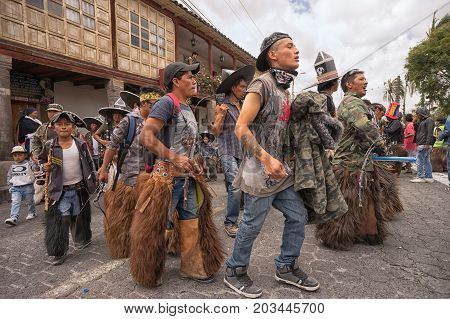 June 24 2017 Cotacachi Ecuador: a group of indigenous kichwa men chanting and dancing at the Inti Raymi parade at summer solstice