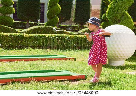 Child playing mini - golf on artificial grass