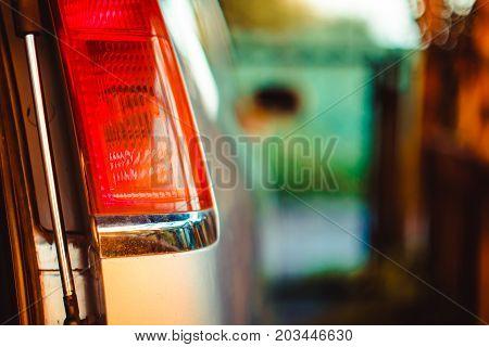 Modern blue car tail light in wet rain drop. Red modern car back light