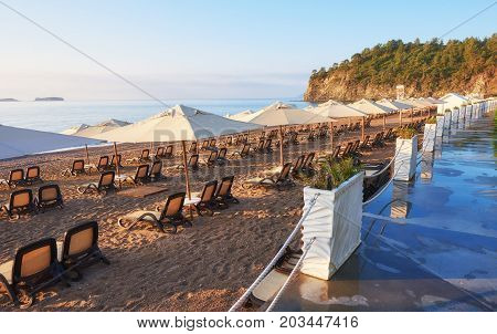 Scenic view of private sandy beach with sun beds from the sea and the mountains. Amara Dols Vita Luxury Hotel. Resort. Tekirova Kemer. Turkey