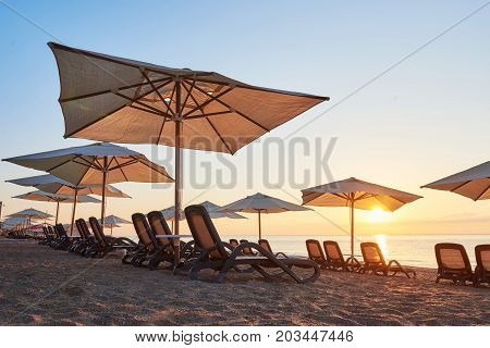 Scenic view of sandy beach with sun beds on the sea and mountains at sunset. Amara Dols Vita Luxury Hotel. Resort. Tekirova Kemer. Turkey.