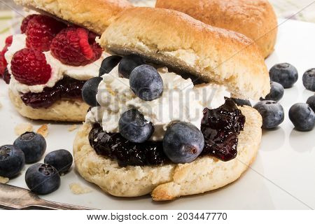 english scone with whipped cream raspberry and blueberry on white cakestand