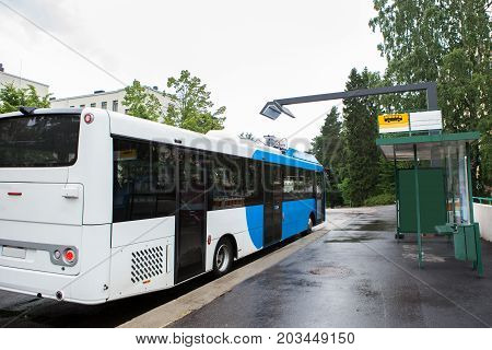 Electric bus at a stop is charged by wireless induction charging