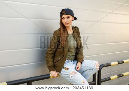 Beautiful Female Model With Freckles In A Baseball Cap In A Green Jacket And T-shirt Sits Near A Met