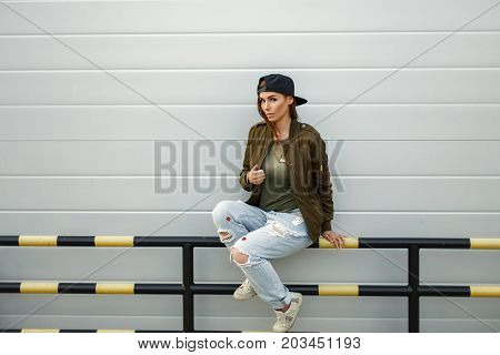 Beautiful Fashionable Woman In Stylish Street Clothes With A Baseball Cap Sits Near A Modern Silvery