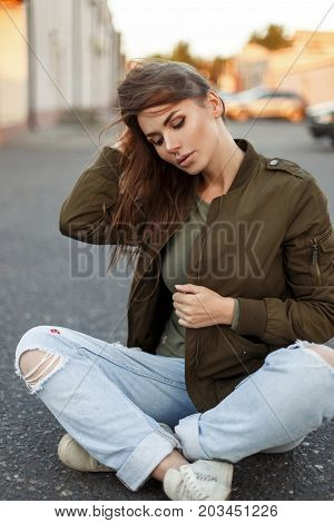 Beautiful Young Woman With Freckles In Trendy Street Clothes Sitting On The Asphalt