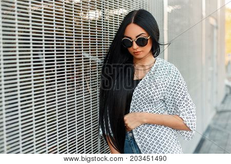 Fashionable Beautiful Woman With Round Sunglasses In A White Cloak Near The Wall Of The Grid