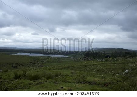 A desolate rural landscape showing a lake, a little forestry and some mountains
