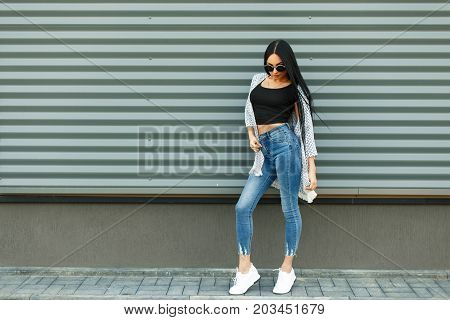 Beautiful Stylish Woman In A Fashionable White Cloak With A Black T-shirt And Blue Jeans With A High