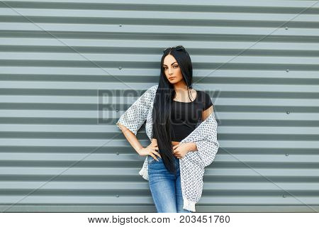 Beautiful Fashionable Girl In A Stylish White Cloak With A Black T-shirt And Blue Jeans Near The Mod
