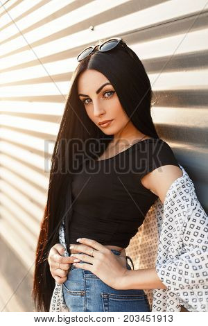 Beautiful Model Woman With A Cute Face With Long Hair In A White Cloak And A Black T-shirt With Jean