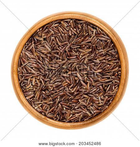 Camargue red rice in wooden bowl. Variety of red wild rice with brownish red colored grains, cultivated in southern France. Isolated macro food photo close up from above on white background.