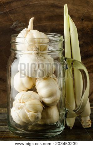 Garlic in mason jar glass with lemon grass on wooden background, food ingredient, spices and herbs