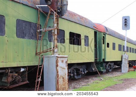 Abandoned green train boxcars alongside train light posts, horizontal aspect