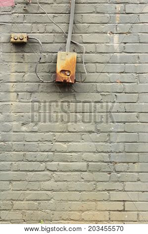 Green painted old brick wall with control box and button, vertical aspect