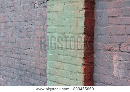 Old brick wall painted in shades of green, purple, and salmon pink with a column, oblique view