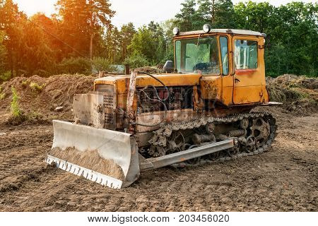 Old excavator working clearing land at sunset of a Sunny day.