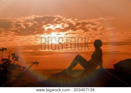 A woman enjoys the sunset and relaxes - enjoying in life