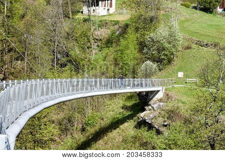 Leontica Switzerland - 17 April 2017: boy walking on the suspension bridge over the river at Leontica on the swiss alps