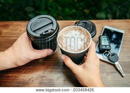 two hands hold cups of coffee on the wooden table top view
