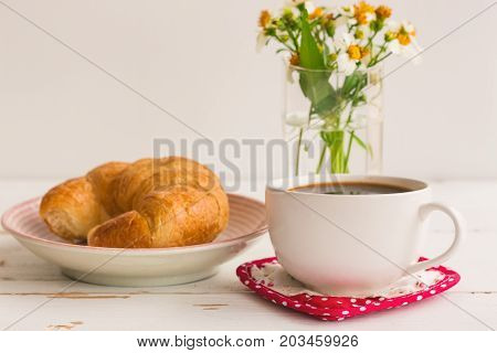 Homemade croissant on plate served with black coffee or americano. Delicious and quick breakfast with fresh croissant and coffee. Croissant and black coffee ready to served for breakfast on wood table. Coffee break with delicious croissant.