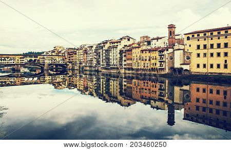 Ponte Vecchio and historical buildings are mirroring in the river Arno Florence Tuscany Italy. Retro photo filter.