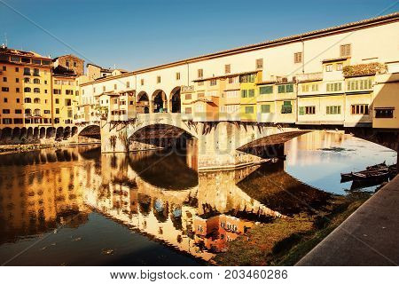 Beautiful Ponte Vecchio is mirroring in the river Arno Florence Tuscany Italy. Travel destination. Yellow photo filter.
