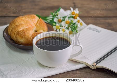 Homemade croissant served with black coffee or americano. Delicious breakfast with fresh croissant and coffee. Croissant and black coffee on wood table with open notebook and pencil with copy space. Coffee break with delicious croissant.