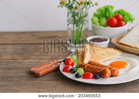 Homemade breakfast with sunny side up fried egg toast sausage fruits vegetable strawberry jam and orange juice in side view with copy space. Delicious homemade american breakfast concept for background. American breakfast with copy space.