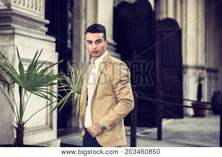 Elegant attractive young man outdoor wearing business suit, in European city