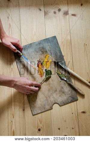 Wooden palette with oil paints yellow red, brushes and palette knife over wooden floor. With female hands in action. Top view with space. Art concept. Atmospheric day light