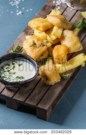 Traditional british fast food fish and chips. Served with white cheese sauce, lime, parsley on wooden serving board over blue concrete background. Close up.