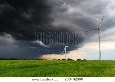 Thunderstorm over a wheat field with wind turbines Wetterau Hesse Germany