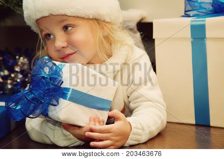 Cute little girl in santa hat lying under the Christmas tree and holding a gift. xmas kid