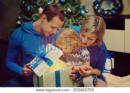young family celebrating Christmas at home. father and mother give a child present. New Year and xmas people