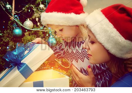 young family celebrating Christmas at home. mother give a child present. New Year and xmas people