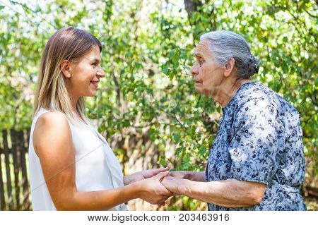 Disabled senior woman posing with friendly caregiver in the park