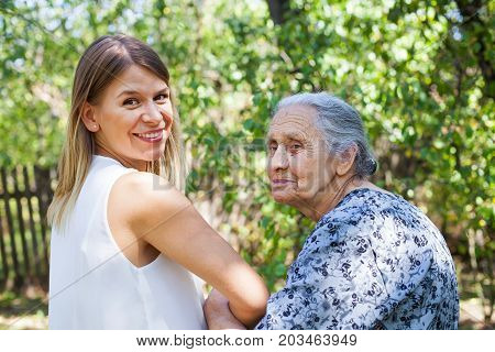 Disabled senior woman walking with friendly caregiver in the park back view