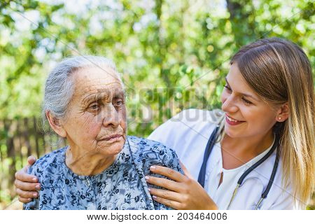 Senior lady with multiple medical conditions spending time with friendly physician in the park