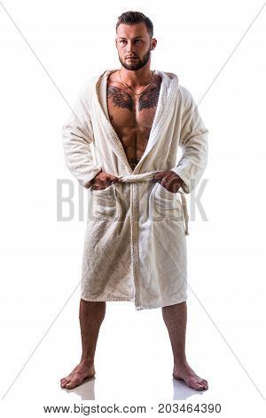 Handsome young muscle man wearing white bathrobe, keeping it open on muscular torso and pecs, isolated on white background