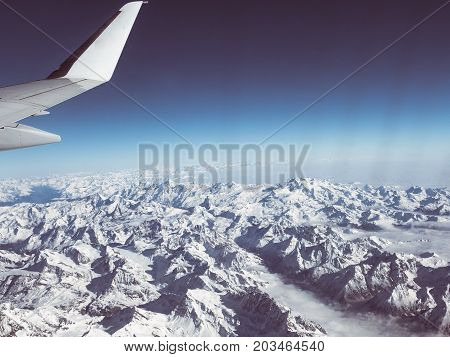 Aerial View Of The Italian Swiss Alps In Winter, With Generic Aeroplane Wing. Snowcapped Mountain Ra