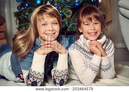 winter home portrait of mother and daughter in sweaters