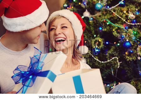 young couple celebrating Christmas at home. man and woman in santa hat with a gift box. New Year and xmas people