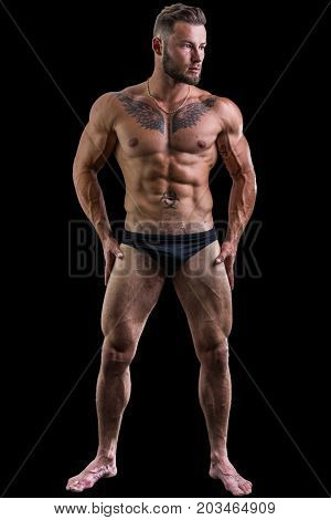 Handsome shirtless muscular man in briefs, standing, isolated on black background. Full length shot