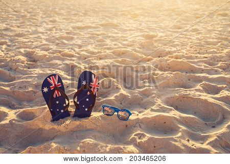 Thongs and sunglasses in sand on a beach Australia day concept