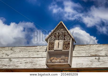 A wooden insect hotel and a beautiful blue sky. Shelter for insects, insect house