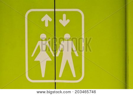 The symbol of a man and a woman with an arrow pointing down and up on a green elevator