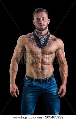 Handsome shirtless muscular man with jeans and black bandanna around his neck, standing, isolated on black background
