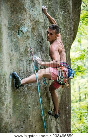 Young male rock climber on challenging route gripping small handholds