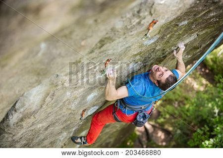Rock climber on challenging route gripping small handholds. View from above.